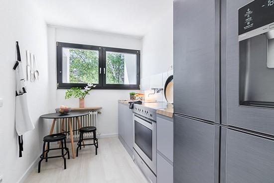 Raum 2 met een cubiqz 2-in-1 reversible keuken met een vrijstaand fornuis- en Amerikaanse koelkast van karton